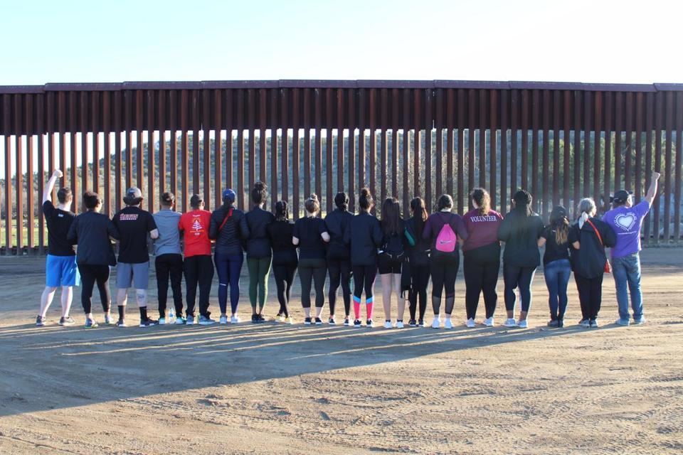 Regis college students stood facing the Mexican border in Southern California.