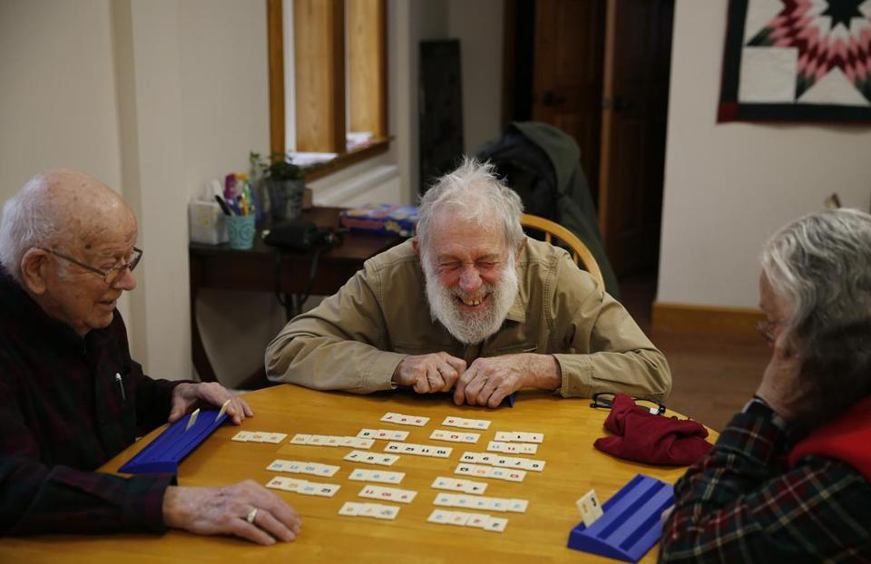 Dover-Foxcroft, ME, 01/16/2019 -- David Migneault, of Garland, (C) laughs as he plays Rummikub with his wife, Peggy, (R) and friend Alden Bent, of Dover-Foxcroft downstairs in Central Hall following a weekly community lunch upstairs at The Commons. Dover-Foxcroft, like nearly all Maine towns, is aging rapidly. But, unlike many other communities, they're planning aggressively for a silver-haired future. (Jessica Rinaldi/Globe Staff) Topic: 20maine Reporter: