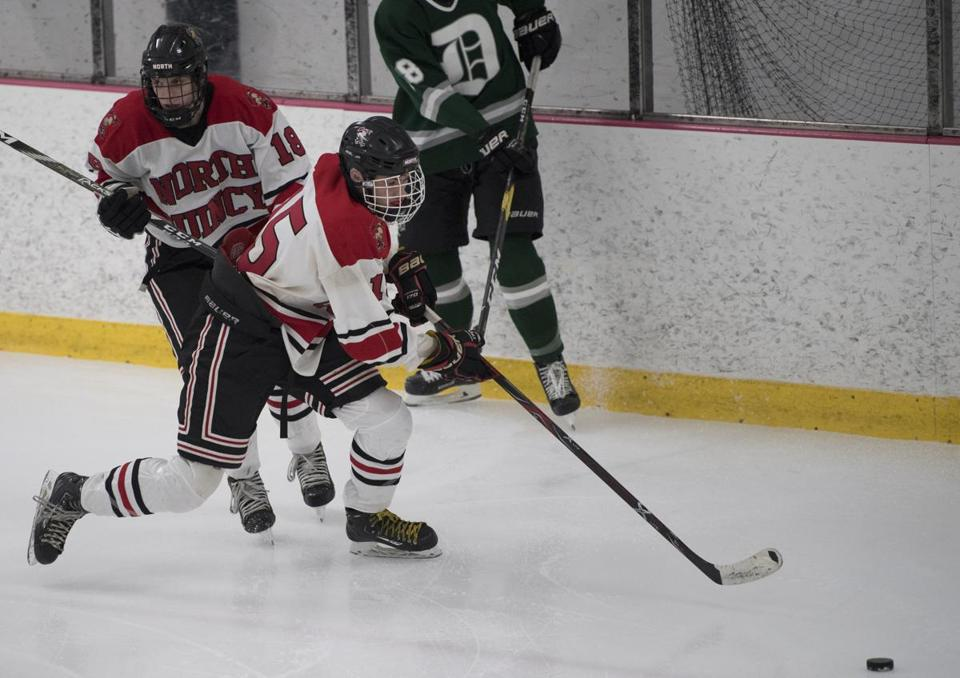 Senior forward Kieran O'Driscoll (15) goes after a loose puck while junior teammate Cormac Flaherty (18) looks up ice for a breakaway opporrunity.