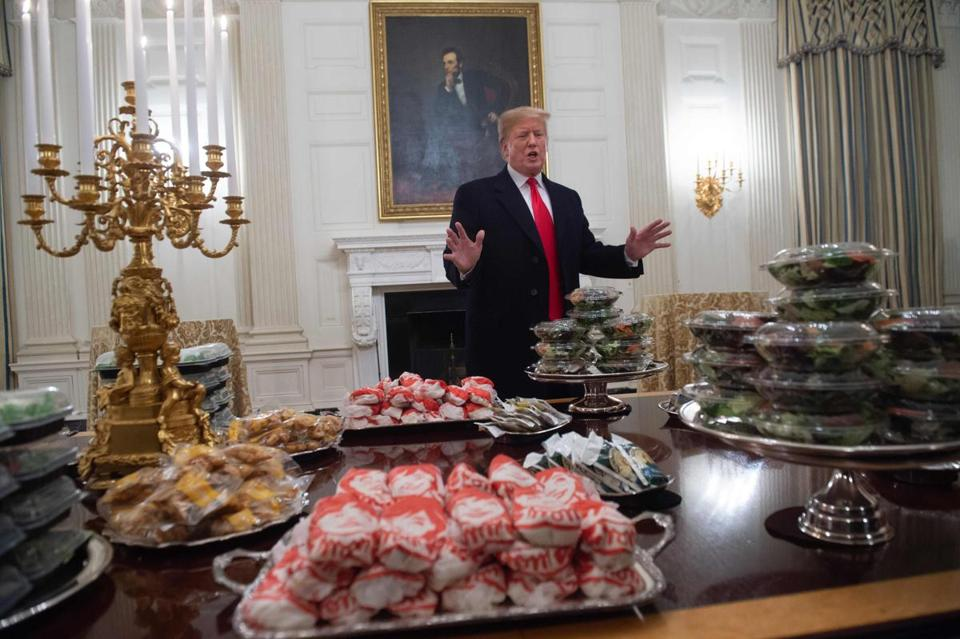 US President Donald Trump speaks alongside fast food he purchased for a ceremony honoring the 2018 College Football Playoff National Champion Clemson Tigers in the State Dining Room of the White House in Washington, DC, January 14, 2019. - Trump says the White House chefs are furloughed due to the partial government shutdown. (Photo by SAUL LOEB / AFP)SAUL LOEB/AFP/Getty Images