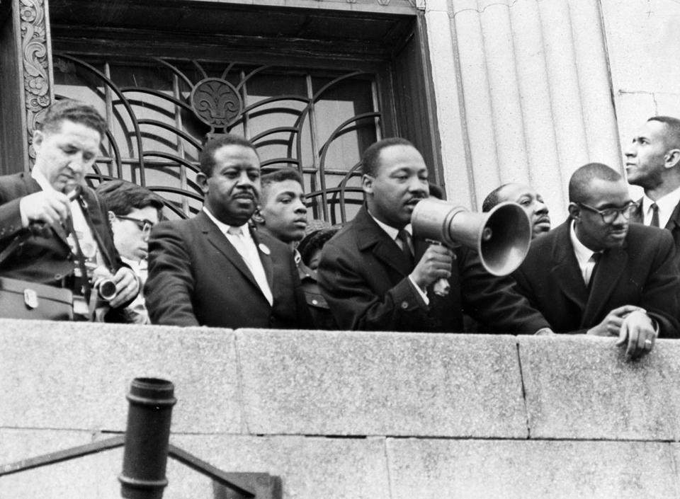 Boston, MA - 4/22/1965: Martin Luther King, Jr. addresses the crowd at the Patrick Campbell School in Roxbury during a visit to Boston, April 22, 1965. Dr. King led a march through the city to protest segregated housing conditions and racially imbalanced schools, and spoke at Boston Common and the State House during his visit. (Paul Connell/Globe Staff) --- BGPA Reference: 160126_MJ_004