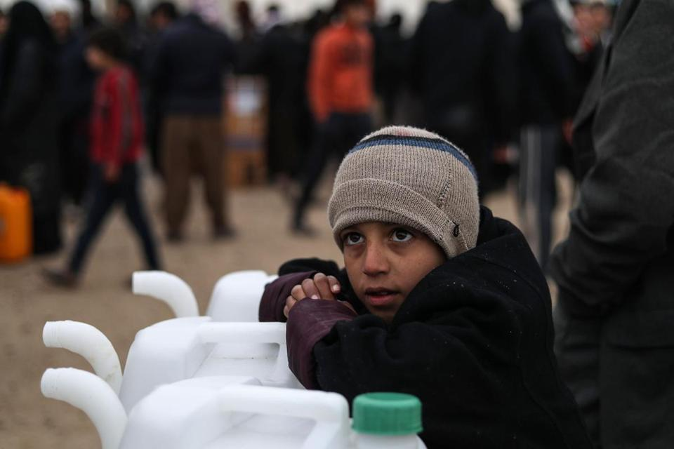 A Syrian boy leans on new jerry cans as he watches aid items to cope with the winter weather being delivered to the al-Hol refugee camp in al-Hasakeh governorate in northeastern Syria on January 07, 2019. (Photo by Delil souleiman / AFP)DELIL SOULEIMAN/AFP/Getty Images