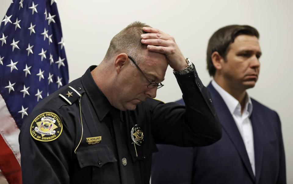 Sebring, Fla., police chief Karl Hoglund wipes his head as he listens to Florida Gov. Ron DeSantis speak during a news conference, Wednesday, Jan. 23, 2019, in Sebring, Fla., after authorities said five people were shot and killed at a SunTrust bank branch. (AP Photo/Chris O'Meara)