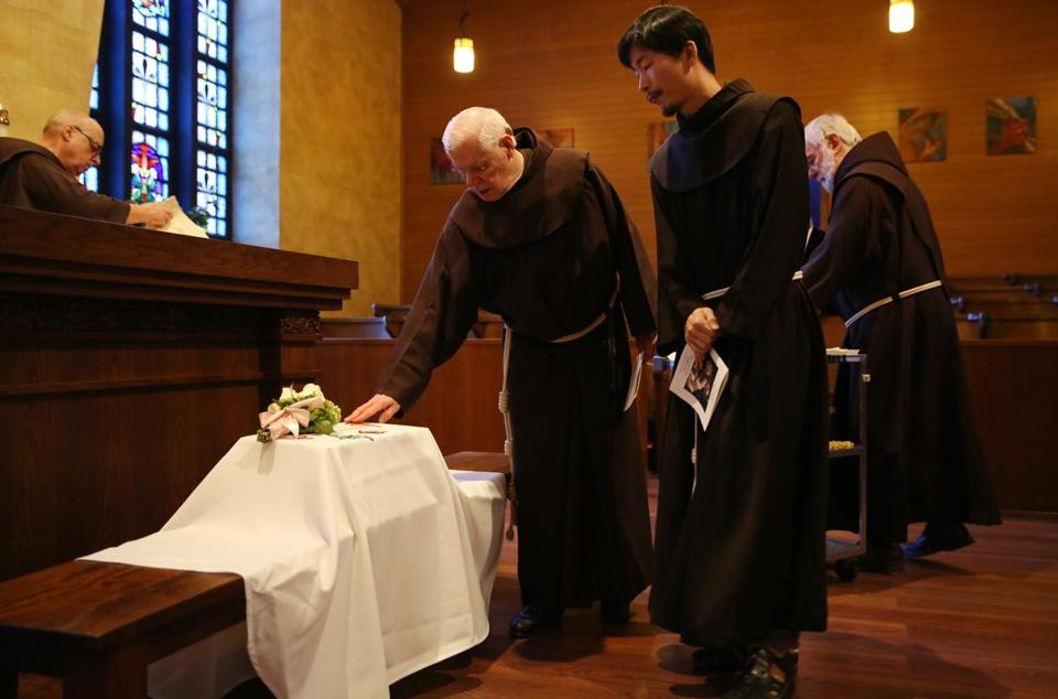 Franciscan Friars pause over over the baby's casket.