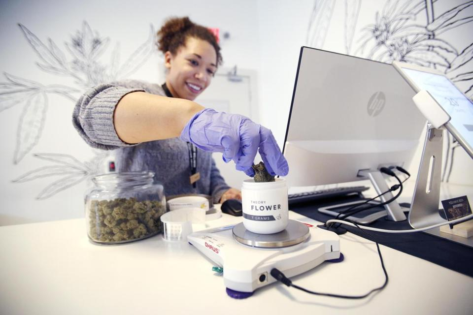Andrea Lawrence measures out an order for a medical marijuana patient trying to beat the lines at Theory Wellness in Great Barrington, Mass., before Friday's opening day for adult-use recreational marijuana on Thursday, Jan. 10, 2019. (Stephanie Zollshan/The Berkshire Eagle via AP)