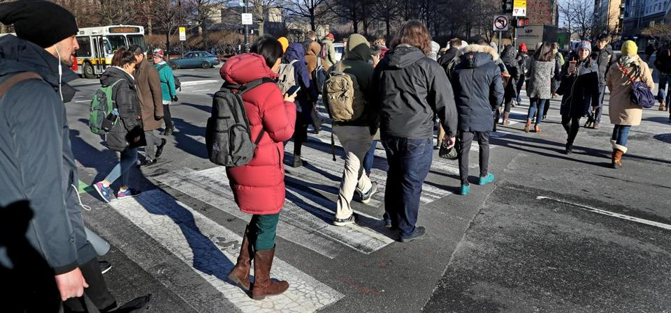 CAMBRIDGE, MA - 1/25/2019: Pedestrians cross Broadway in Cambridge. Cambridge has six subway stops, several major bus lines, and bike lanes everywhere. It's minutes from downtown Boston, densely packed over just 6.4 square miles, and has enacted several public policies aimed at severely reducing carbon emissions. Yet even Cambridge can't seem to get its residents to give up their cars — or, at least, not as quickly as officials would like. (David L Ryan/Globe Staff ) SECTION: METRO TOPIC