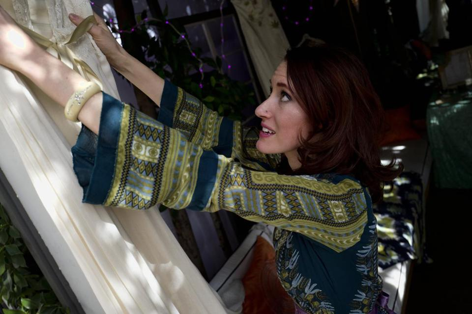 Janay A. owner and designer of High Vibe Bride from Kansas City, hangs one of her creations made from hemp silk at her display at the High Vibe Bride booth during the Cannabis Wedding Expo in Los Angeles on Saturday, Jan. 26, 2019. (AP Photo/Richard Vogel)