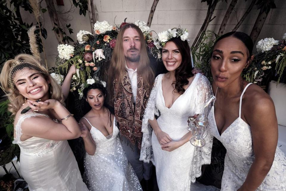 Philip Wolf, CEO of the Cannabis Wedding Expo poses with models wearing wedding dresses designed by High Vibe Bride, Simply Bridal, and Davids Bridal in Los Angeles on Saturday, Jan. 26, 2019 during the Cannabis Wedding Expo. (AP Photo/Richard Vogel)