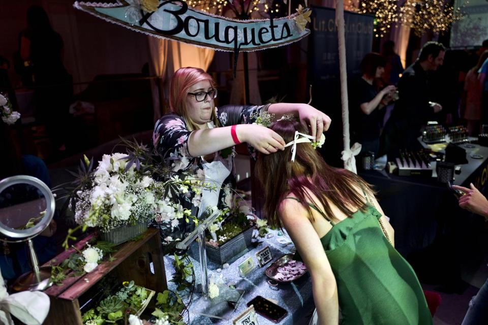 Jordyn Switzer with Bitchin' Bouquets a floral service for all occasions, try on a visitor a floral headband using cannabis flowers during the Cannabis Wedding Expo in Los Angeles on Saturday, Jan. 26, 2019. (AP Photo/Richard Vogel)
