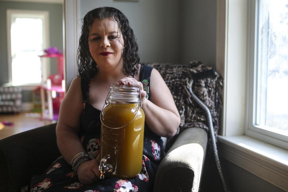 Dedham, MA--02/01/2019--Joanna Varner, 36, of Weymouth, poses for a portrait with her marijuana-infused mango tea on Friday afternoon. Varner is a medical marijuana patient who dreams of starting a business -- Ladies Lifted Kitchen -- making organic, gourmet cannabis-infused cookies, brownies, granola, and tea. (Nathan Klima for the Boston Globe) Topic: 03illicitpot Reporter: