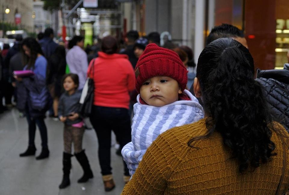 A woman holds a child in a line snaking around the block outside a U.S. immigration office with numerous courtrooms Thursday, Jan. 31, 2019, in San Francisco. The crowd was mixed with people who had court appointments for Thursday, people whose appointments were swallowed up by shutdown and others who had 'Notices to Appear' but assumed that meant they had court dates. (AP Photo/Eric Risberg)