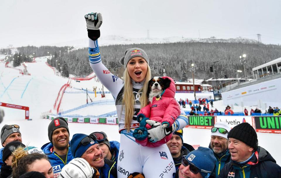 Lindsey Vonn celebrated with the US skiing team and her dog Lucy after winning the bronze medal in the women's downhill event of the Alpine Ski World Championships.