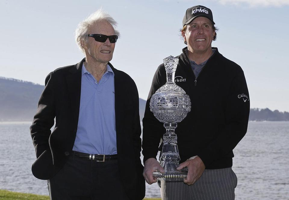 Phil Mickelson poses with his trophy and Clint Eastwood on the 18th green of the Pebble Beach Golf Links after winning the AT&T Pebble Beach Pro-Am golf tournament Monday, Feb. 11, 2019, in Pebble Beach, Calif. (AP Photo/Eric Risberg)