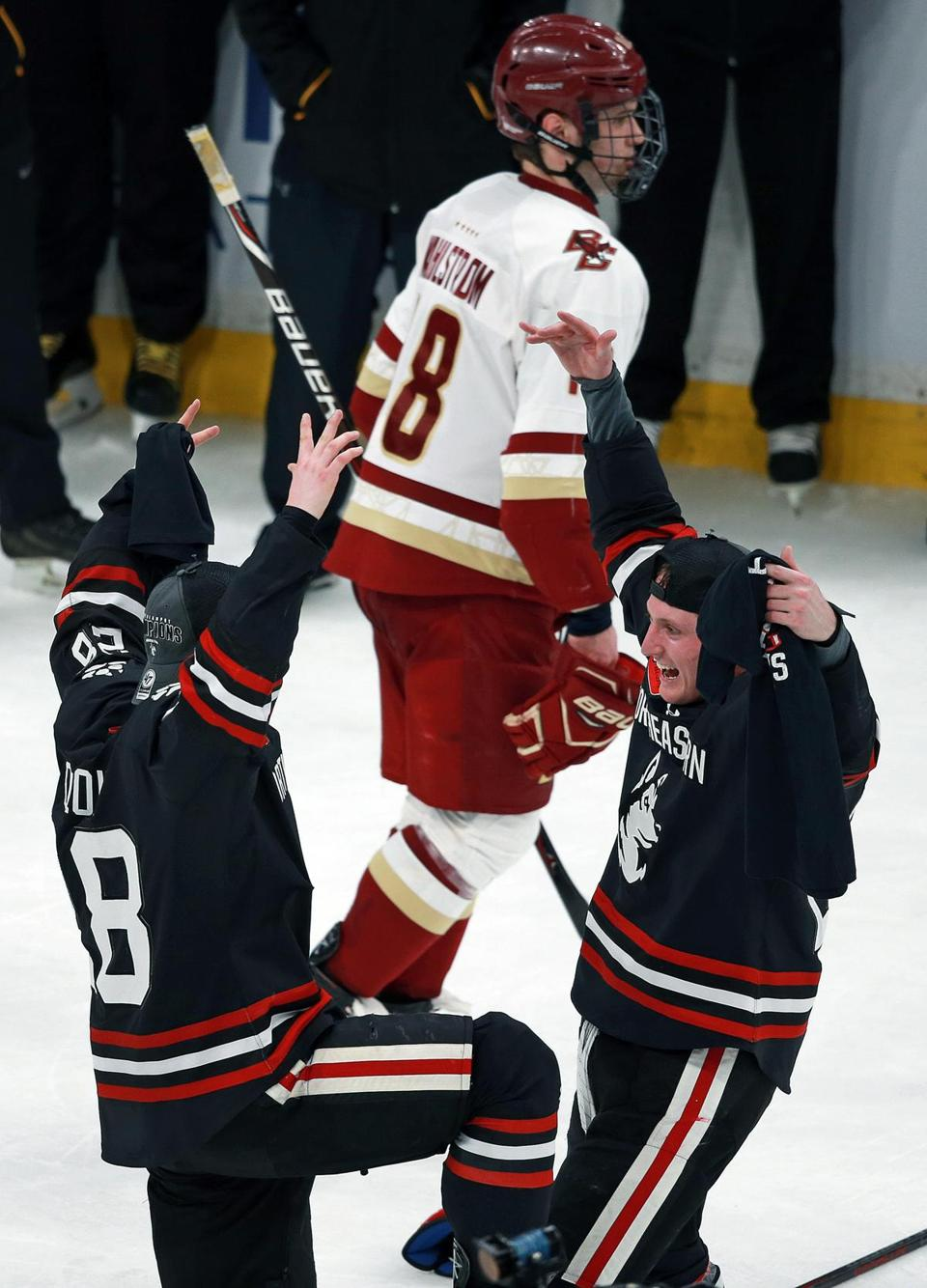 Northeastern's Zach Solow (left) and Patrick Schule rejoice as BC's Oliver Wahlstrom skates off.