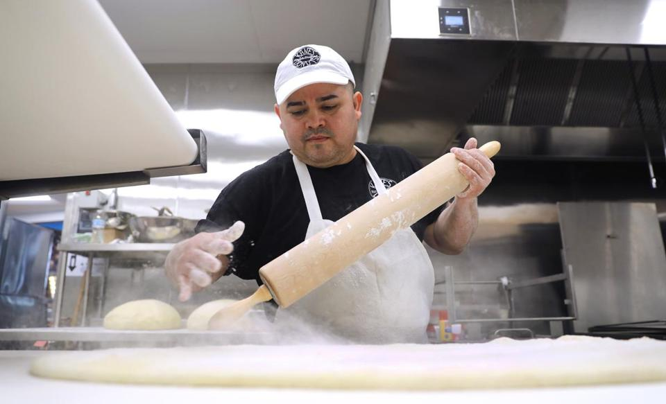 Saugus, MA - 2/13/19 Head baker Rigoberto Cartagena (cq) flours dough on the sheeter. Kane's Donuts (cq) is opening a new location in Saugus, near the orange dinosaur. (The shop and the dinosaur date from the 1950s.) Co-owner and president Paul Delios (cq) said the expected hard opening will be by March 1. Photo by Pat Greenhouse/Globe Staff Topic: Kane's Reporter: Jon Chesto