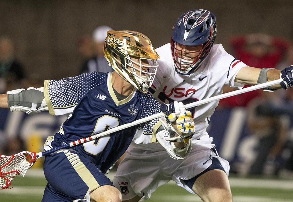 Allston, MA.--June 28, 2018-- Stan Grossfeld/Globe Staff--- Kieran McArdle of the MLL All Stars tries to get past Team USA midfielder Michael Ehrhardt during the MLL All Star game at Harvard Stadium.