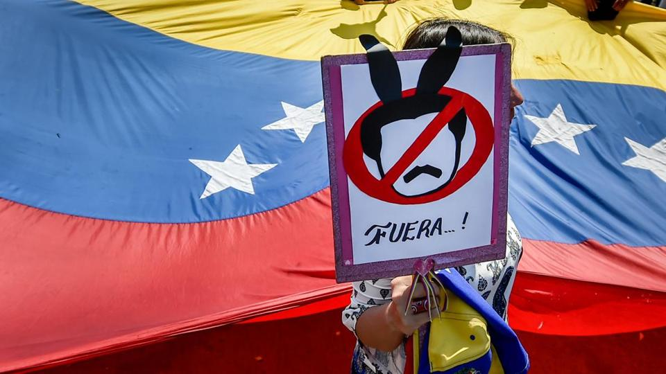 "A demonstrator holds a placard as she takes part in a protest of Venezuelans against the government of President Nicolas Maduro at the Simon Bolivar International bridge in Cucuta, Colombia, on the border with Venezuela, on February 15, 2019. - The US Treasury announced Friday it was imposing sanctions on five intelligence and security officials close to crisis-hit Venezuela's ""former"" President Nicolas Maduro. Those targeted are ""aligned with illegitimate former President Nicolas Maduro, who continue to repress democracy and democratic actors in Venezuela,"" a Treasury Department statement read. (Photo by Luis ROBAYO / AFP)LUIS ROBAYO/AFP/Getty Images"
