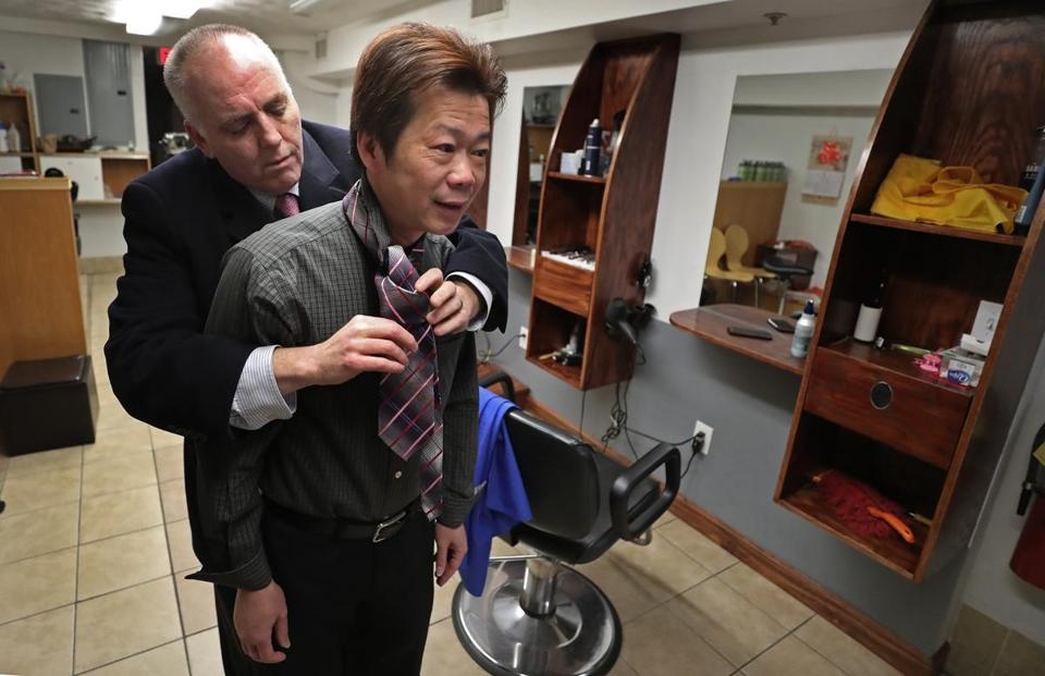 BOSTON, MA - 2/14/2019: Boston city councilor Ed Flynn helps Yan Chi Chen with his tie before going to court at his chinatown shop. Chen has runs a hair salon at 106 Tyler St in Boston's Chinatown, which is a row house with 4 apartments above a ground floor commercial space. He is facing eviction, a court trial at the Edward Brooks courthouse. But before leaving for court there was a small rally for him in Chinatown.....they met at the salon before going to courthouse. (David L Ryan/Globe Staff ) SECTION: METRO TOPIC 15chinatown