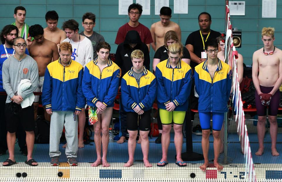 Members of the Acton-Boxboro High School swin team (in yellow and blue jackets) stood for a solemn moment of silence before the Division 1 swim meet at Boston University in memory of their late coach, Jeff Jones, who died suddenly on Friday at age 74.