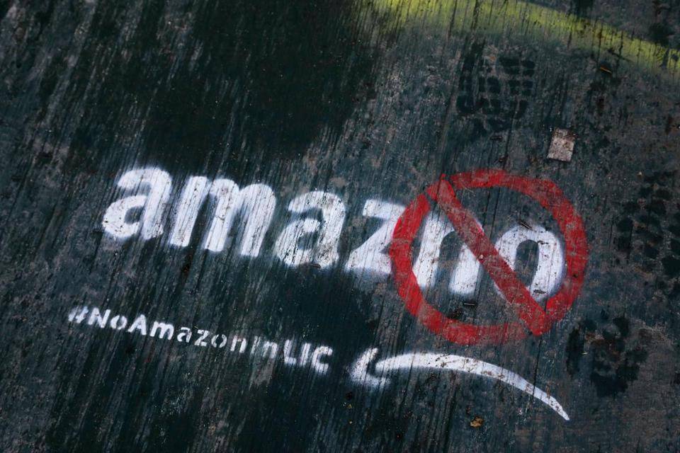 FILE - In this Nov. 16, 2018, file photo graffiti has been painted on a sidewalk by someone opposed to the location of an Amazon headquarters in the Long Island City neighborhood in the Queens borough of New York. Local opposition to the proposed Amazon campus grew quickly with grievances that the deal was done secretively; Amazon didn't need nearly $3 billion in tax incentives; and rising rents could push people out of the neighborhood. (AP Photo/Mark Lennihan, File)