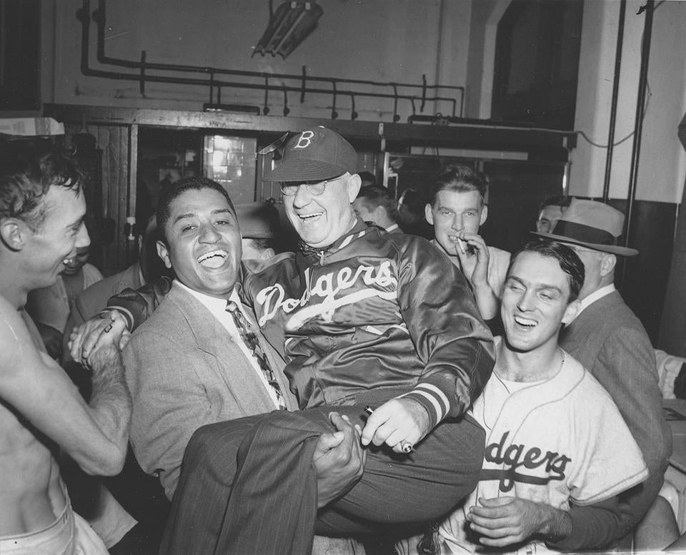 FILE - In this Oct. 2, 1949, file photo, Brooklyn Dodgers pitcher Don Newcombe, second from left, holds up Dodgers manager Burt Shotton in the Dogers dressing room after they won the National League pennant against the Philadelphia Phillies, in Philadelphia, October 2, 1949. Other players are unidentified. (AP Photo/File)