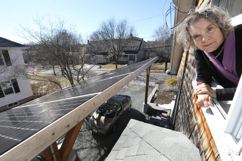 Jocelyn Tager, who has pushed for an ordinance requiring new construction in Watertown to include green energy, looks out at the solar pergola over her driveway.