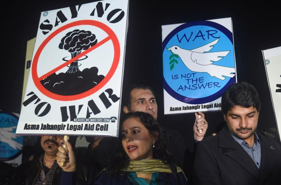 "TOPSHOT - People hold signs reading ""Say no to war"" and ""War is not the answer"" during a vigil for peace in Lahore on March 3, 2019. - Tensions between India and Pakistan raged on March 2 as heavy firing by their armies killed at least seven people on either side of their fiercely disputed Kashmir border. Tensions have soared since a suicide bombing in Kashmir last month claimed by Pakistan-based militants killed 40 Indian paramilitaries. (Photo by ARIF ALI / AFP) (Photo credit should read ARIF ALI/AFP/Getty Images)"