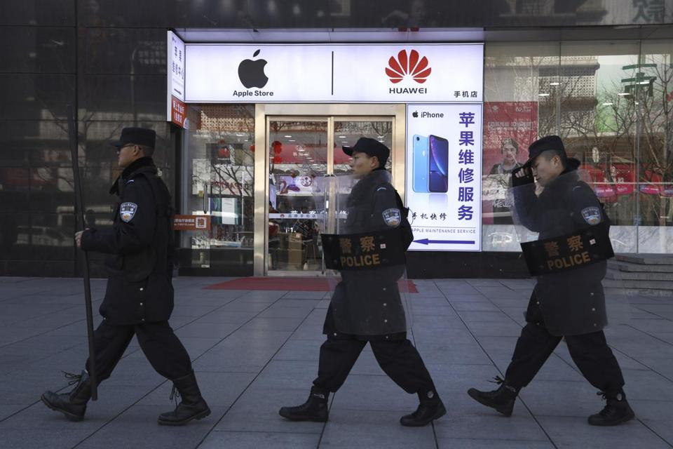 Security guards march past a shop selling Apple and Huawei phones in Beijing, China, Wednesday, March 6, 2019. China's emergence as a competitor in key technologies has rattled Washington and other governments that worry Chinese competition is a threat to their industries and employment. Such concerns underscore a standoff between the U.S. and China over Huawei Technologies, the world's biggest maker of telecom infrastructure for new high-speed 5G networks. Washington has been pushing hard to exclude the Chinese company from building the backbone of the future internet. (AP Photo/Ng Han Guan)