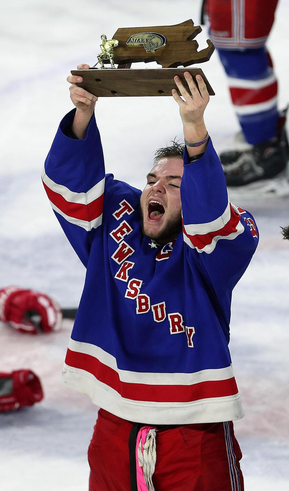 Tewksburycaptain Aaron Scott celebrates by hoisting the MIAA Div. 2 North trophy following his team's victory over Boston Latin, 6-4.