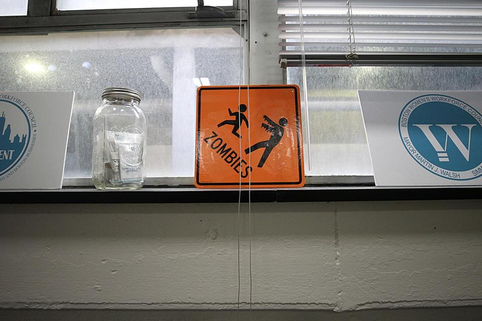 "An orange construction-zone-like sign with the word ""zombies"" and a figure with outstretched arms chasing a smaller figure sits on the windowsill — left over from a Halloween party."