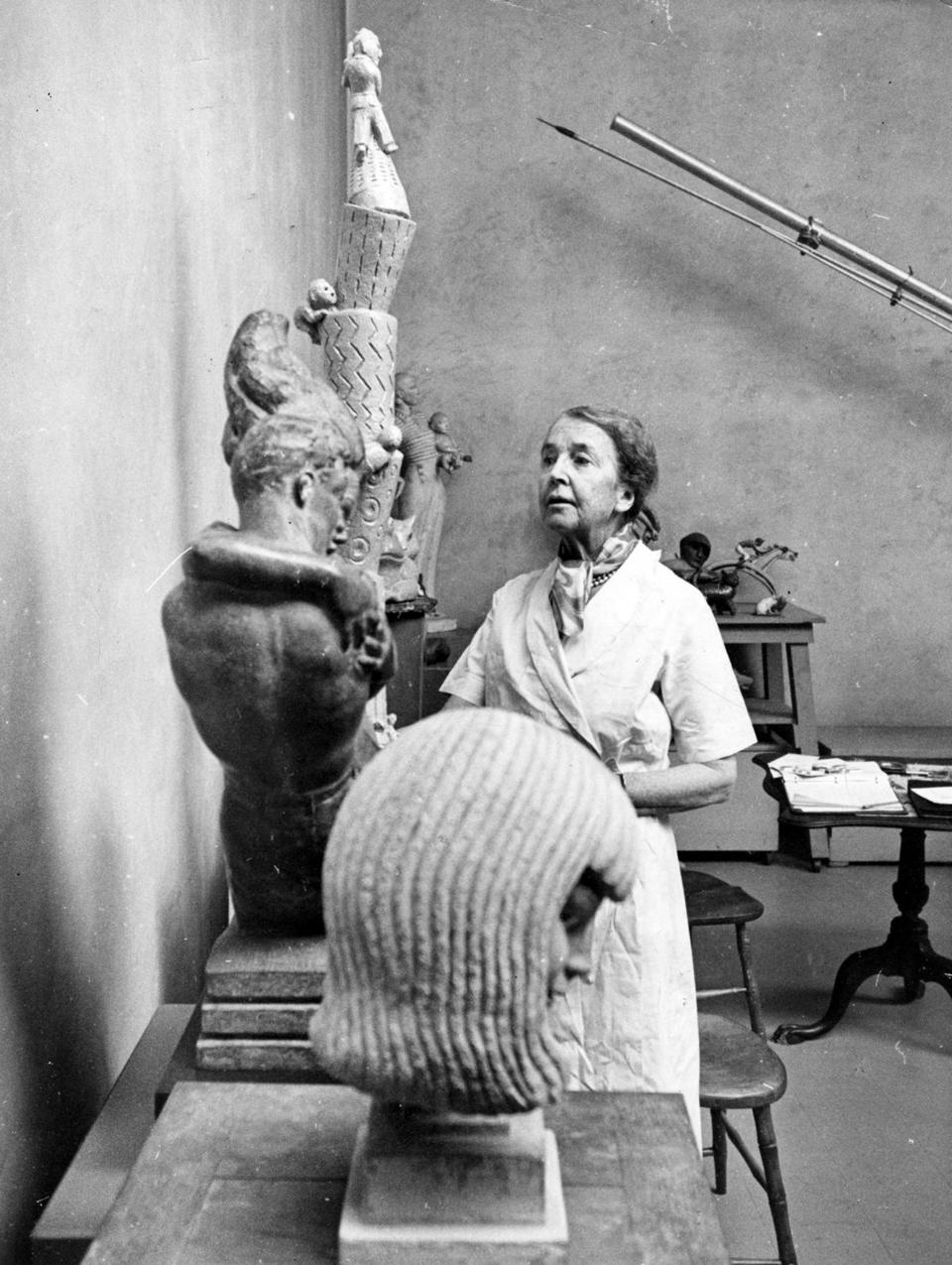 "Dover, MA: Sculptor Amelia Peabody stands with some of her work, including ""Rocket Test,"" the tallest at left, on Dec. 29, 1962."