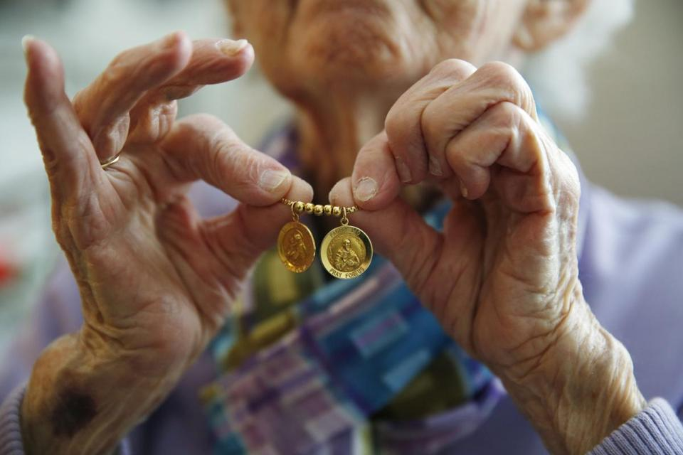 Marlborough, MA, 03/13/2019 -- Dottie Creamer, 92, holds out the necklace she wears with Saint Anthony and Padre Pio, she picked it up from her old apartment for good luck the day she moved into Christopher Heights, an assisted living residence in Marlborough. (Jessica Rinaldi/Globe Staff) Topic: xxseniorhousing Reporter: