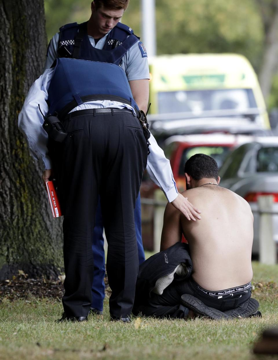 Police officers consoled a man after the first reported mosque shooting.