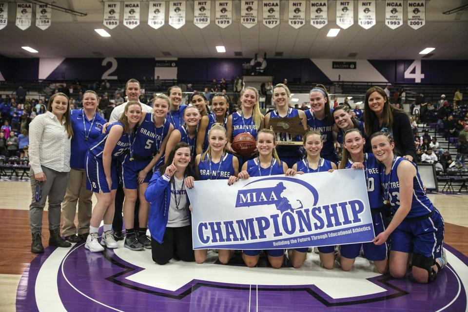 Worcester, MA--03/16/2019--The Braintree girl's basketball teams poses with the championship banner and trophy after defeating Springfield Central in the MIAA D1 girl's basketball final in Worcester on Saturday afternoon. (Nathan Klima for The Boston Globe) Topic: 17schholycross Reporter: