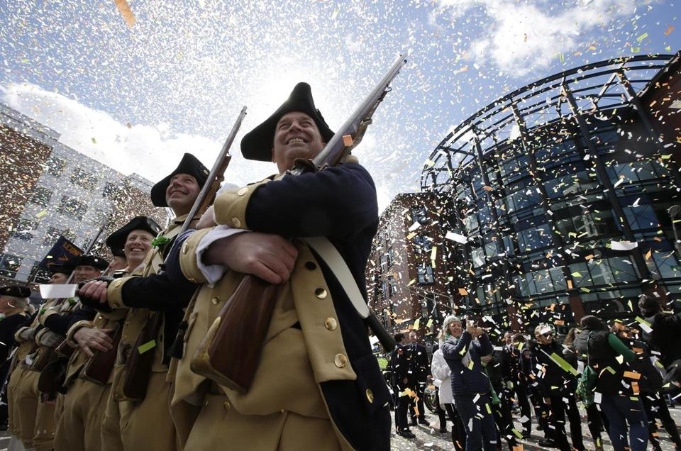 Lexington Minutemen Revolutionary War re-enactors held their rifles as confetti falls at the start of the annual St. Patrick's Day Parade.