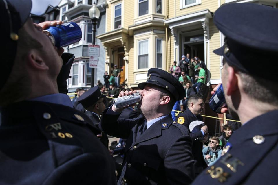 Men in uniform chugged drinks during the St. Patrick's Day Parade in South Boston on Sunday afternoon.