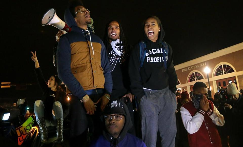 In this Nov. 24, 2014 file photo, Ferguson activist Daren Seals, top center, awaits the decision by a grand jury on whether to indict Darren Wilson in the death of Michael Brown in front of the police station in Ferguson , Mo. Six young men with connections to the Ferguson protests, including Seals, have died, drawing attention on social media and speculation in the activist community that something sinister is at play.