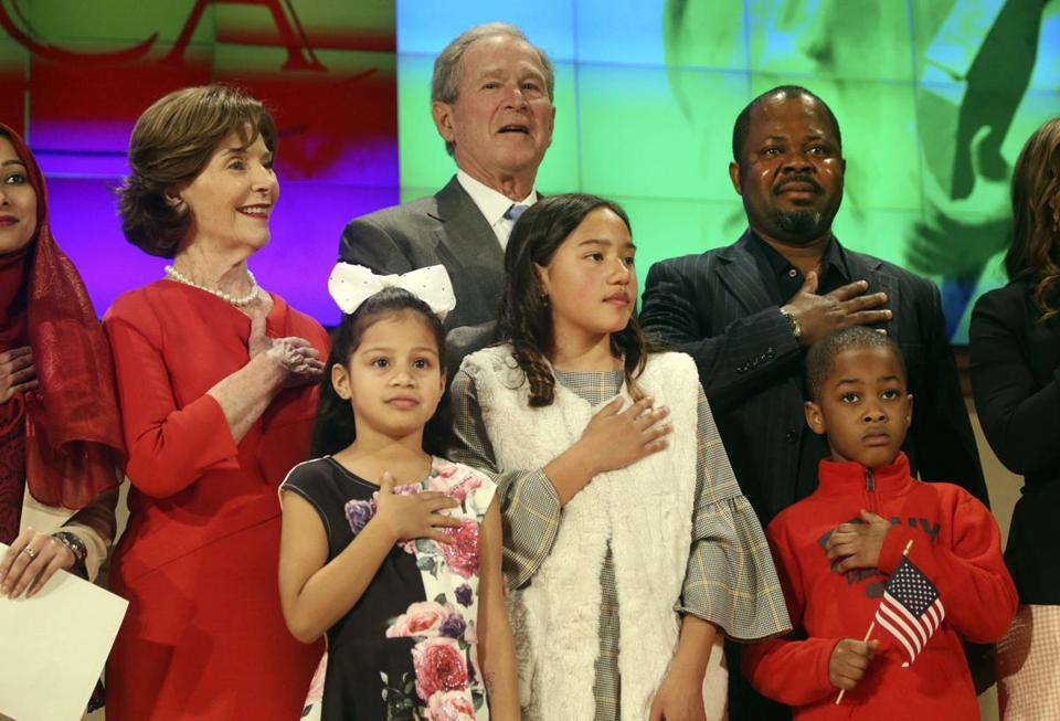 Former President George W. Bush and former first lady Laura Bush recite the pledge of allegiance with new U.S. citizens, including Felix Odeh, (top right) of Nigeria, during a naturalization ceremony at the George W. Bush Presidential Center in Dallas on Monday, March 18, 2019. Forty-nine people representing 20 countries became American citizens at the ceremony. (Rose Baca/The Dallas Morning News via AP)
