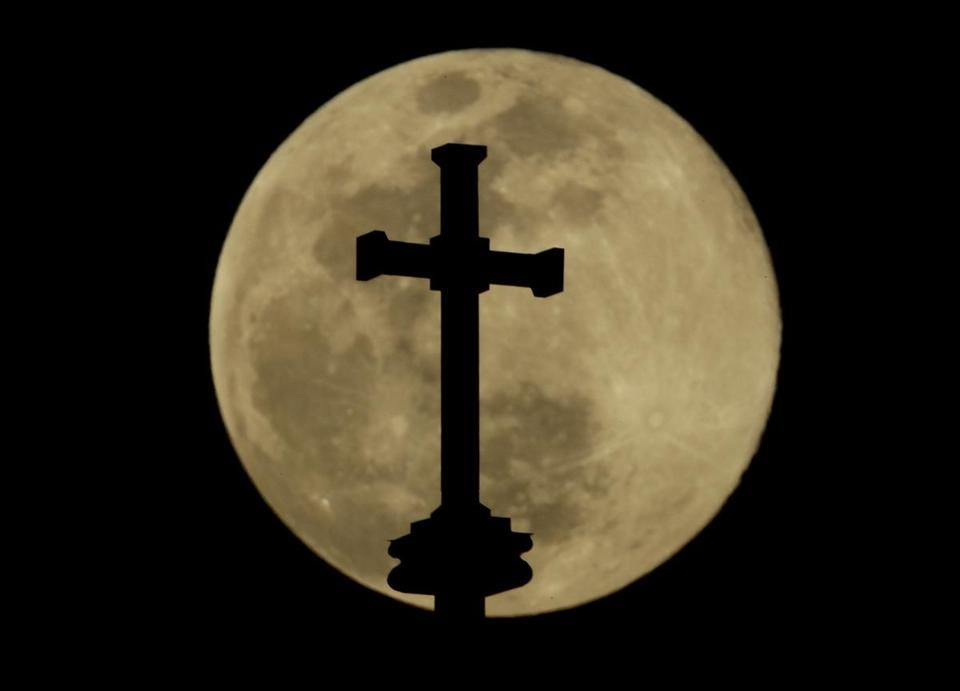 A cross on top of the Holy Family Cathedral is silhouetted against the rising full moon Wednesday, March 20, 2019, in Tulsa, Okla. (AP Photo / Charlie Riedel)