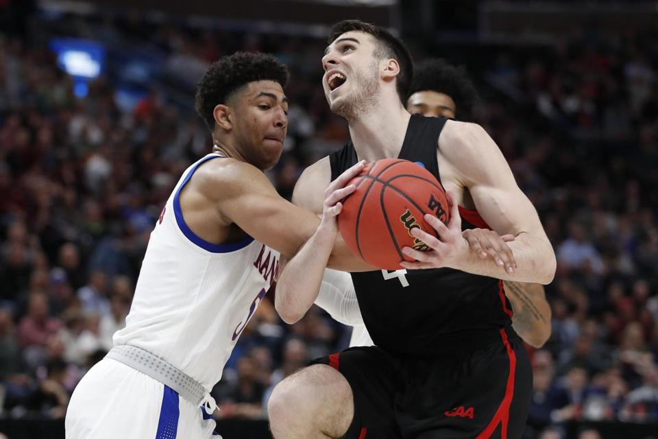 Kansas guard Quentin Grimes (5) fouls Northeastern guard Vasa Pusica (4) in the second half during a first round men's college basketball game in the NCAA Tournament, Thursday, March 21, 2019, in Salt Lake City. (AP Photo/Jeff Swinger)