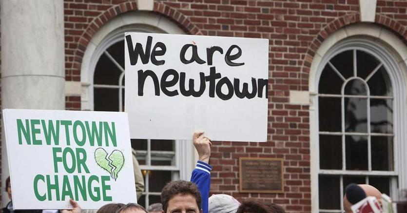 Residents held placards during a gathering outside Edmond Town Hall to observe the six-month anniversary of the massacre at Sandy Hook Elementary School in Newtown on June 14, 2013.