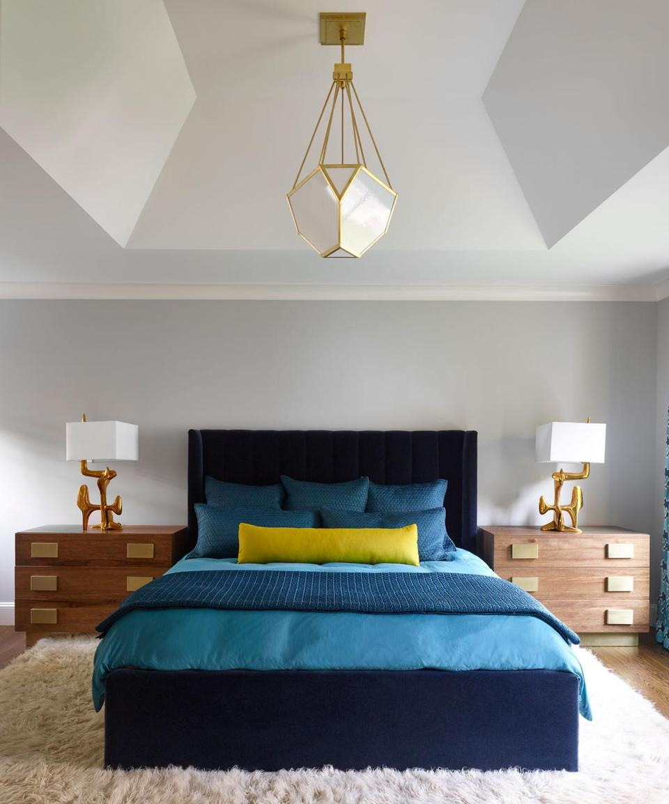 An extra-long chartreuse lumbar pillow provides a pop of offbeat color in the master bedroom. A faceted pendant light from The Urban Electric Company echoes the lines of the ceiling.
