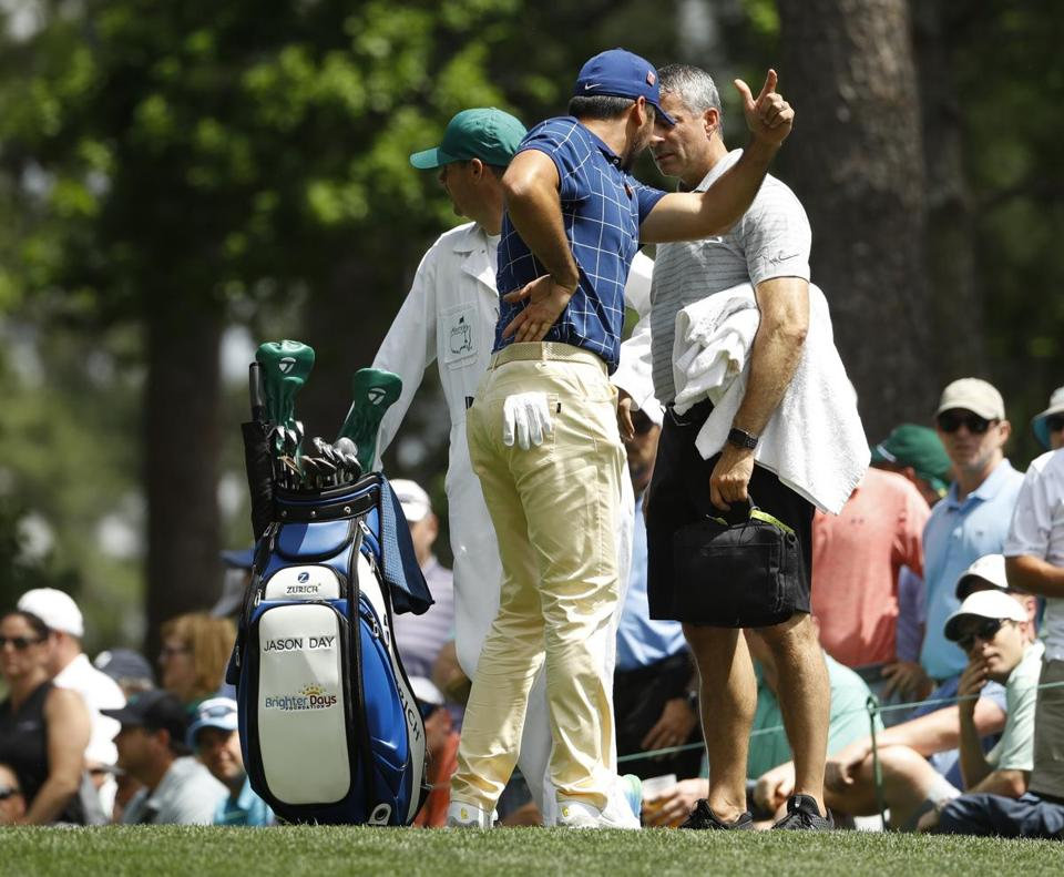 Jason Day holds his back on the fourth tee during the first round Thursday of the Masters.