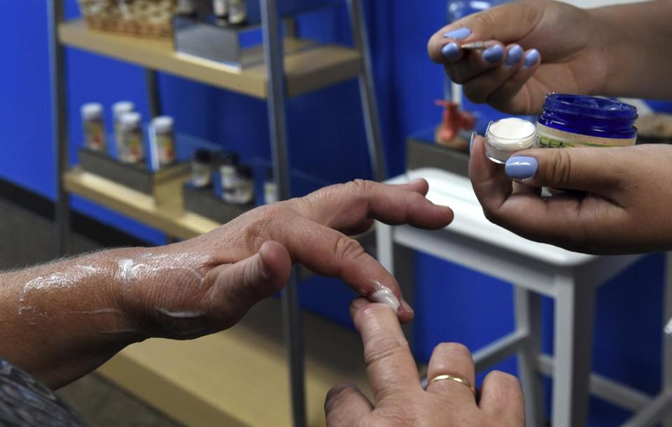 FILE - In this Aug. 29, 2018, file photo, a customer tries a free sample of a pain cream that contains cannabidiol (CBD) for her arthritis at Minnesota Hempdropz in Maplewood, Minn. Mainstream retailers are leaping into the world of products like skin creams and oils that tout such benefits as reducing anxiety and helping you sleep. The key ingredient is CBD, or cannabidiol, a compound derived from hemp and marijuana that doesn't cause a high. (Jean Pieri/Pioneer Press via AP, File)