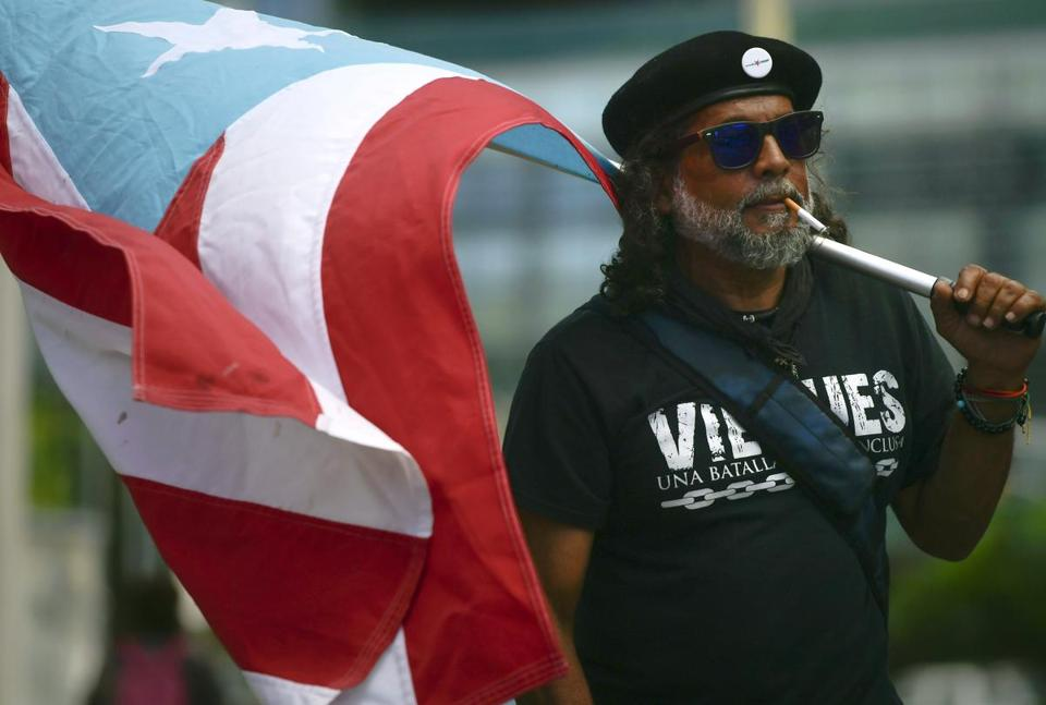 A protester carries a Puerto Rican flag during a protest against the Federal Fiscal Control Board, as part of the May Day celebration, in San Juan, Puerto Rico, Wednesday, May 1, 2019. The U.S. Congress established the appointed Fiscal Control Board to oversee the debt restructuring in order to combat the Puerto Rican government-debt crisis. (AP Photo/Carlos Giusti)