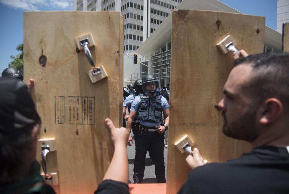 Demonstrators holding wooden shields are confronted by police during a protest against the Federal Fiscal Control Board, as part of the May Day celebration, in San Juan, Puerto Rico, Wednesday, May 1, 2019. The U.S. Congress established the appointed Fiscal Control Board to oversee the debt restructuring in order to combat the Puerto Rican government-debt crisis. (AP Photo/Carlos Giusti)