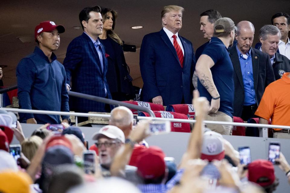 President Donald Trump, center, and first lady Melania Trump, third from left, accompanied by Rep. Matt Gaetz, R-Fla., second from left, Sen. David Perdue, R-Ga., fifth from left, and Rep. Mark Meadows, R-N.C., right, arrive for Game 5 of the World Series baseball game between the Houston Astros and the Washington Nationals at Nationals Park in Washington, Sunday, Oct. 27, 2019. (AP Photo/Andrew Harnik)