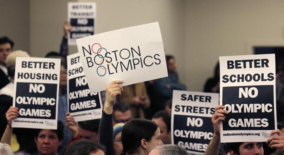 Boston Olympic opponents held signs during a public forum in February.