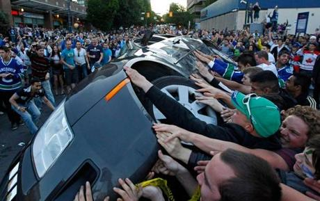 After Game 7, people in Vancouver turned over a car as part of an ugly display of rioting.