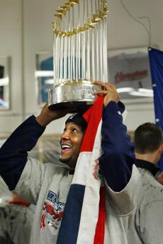 Martinez, hoisting the World Series trophy, collected one of the four wins in the series.